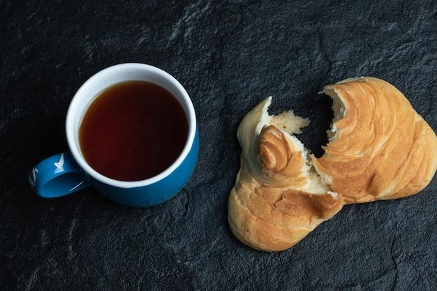 Délicieuse pâtisserie avec une tasse de thé sur fond noir.