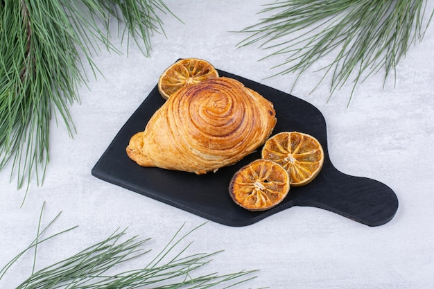 Délicieuse pâtisserie avec des tranches d'orange séchées sur tableau noir. photo de haute qualité