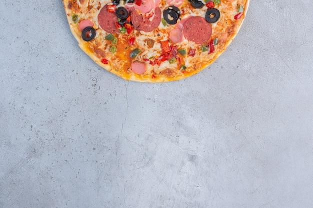 Délicieuse pizza affichée sur fond de marbre.