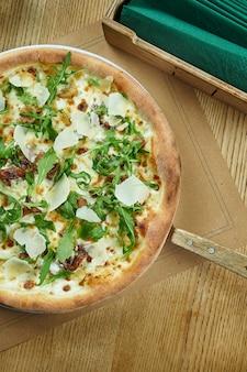 Délicieuse pizza au fromage, champignons sauvages, roquette de girolles et parmesan sur une table en bois. cuisine traditionnelle italienne. vue de dessus. nourriture pour le déjeuner