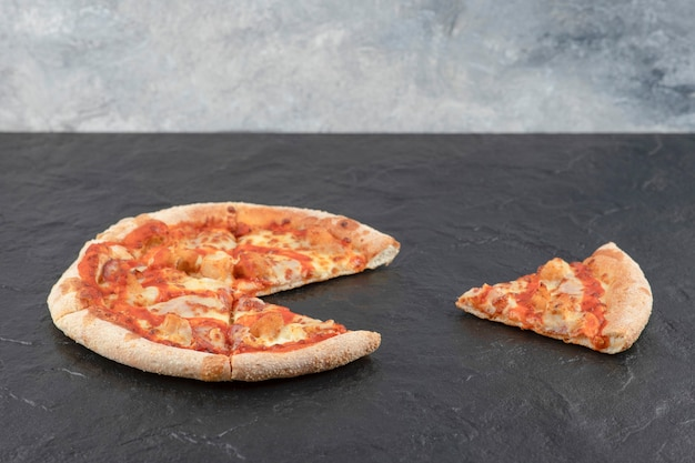 Délicieuse pizza au poulet buffalo épicé sur une surface noire.