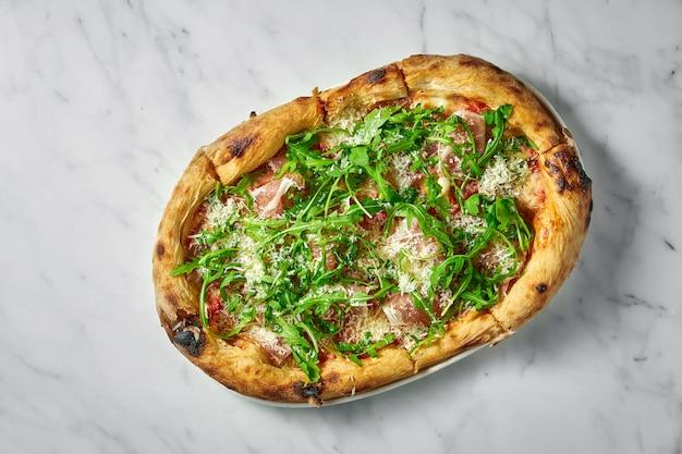 Délicieuse pizza au prosciutto, sauce tomate, parmesan et roquette sur plaque blanche sur marbre blanc