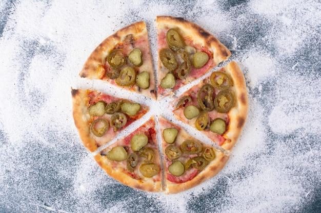 Délicieuse pizza au salami avec des piments jalapenos sur marbre.