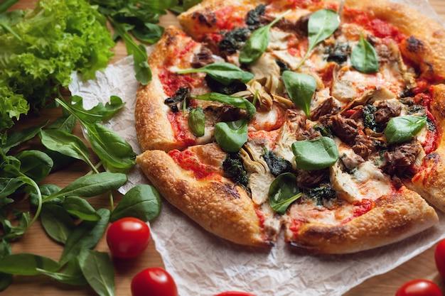 Délicieuse pizza aux artichauts et thon servie sur table en bois