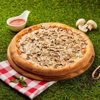 Délicieuse pizza aux champignons et fredonner sur l'herbe verte