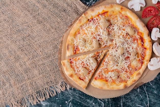 Délicieuse pizza aux champignons avec fromage et légumes frais sur marbre.