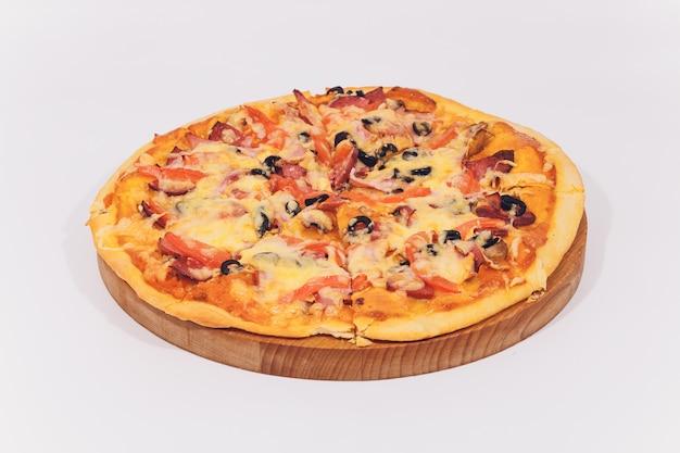 Délicieuse pizza aux fruits de mer sur support en bois isolé sur blanc.