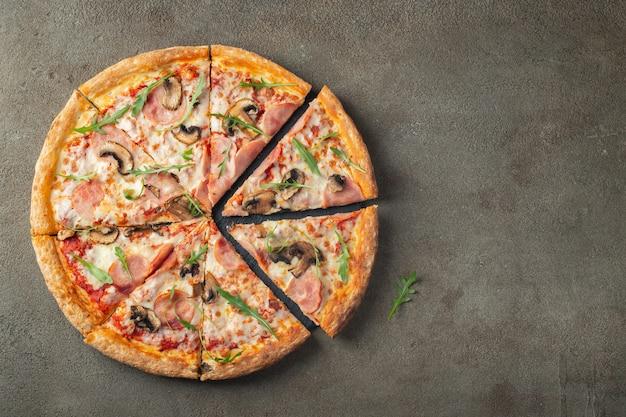 Délicieuse pizza chaude au jambon et aux champignons.