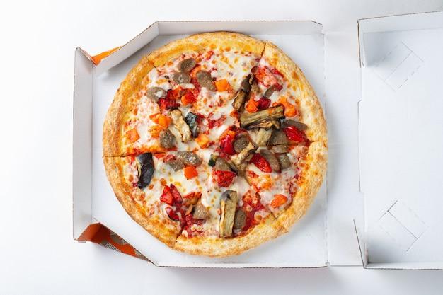 Délicieuse pizza chaude dans une boîte avec du jambon.
