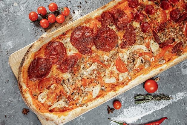 Délicieuse pizza avec filet de poulet, jambon, bacon, saucisses, sauce tomate et mozzarella