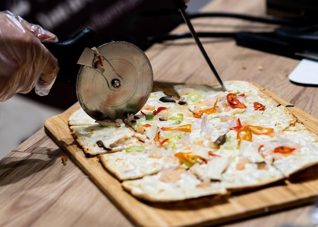 Délicieuse pizza fraîche, gros plan de coupe de pizza sur pizza italienne sur une table en bois