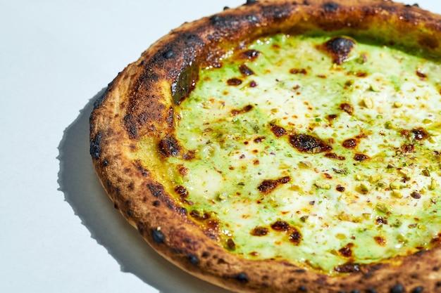 Délicieuse pizza italienne au feu de bois avec mozzarella, ricotta, parmesan et pistaches sur une surface grise. lumière forte.