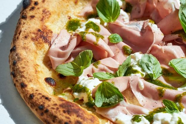 Délicieuse pizza italienne au feu de bois avec sauce crémeuse, mortadelle, pesto et basilic sur une surface grise. lumière forte.