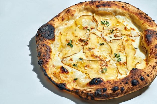 Délicieuse pizza italienne au feu de bois avec sauce crémeuse, noix de cajou, poire, mozzarella et gorgonzola sur une surface grise. lumière forte.