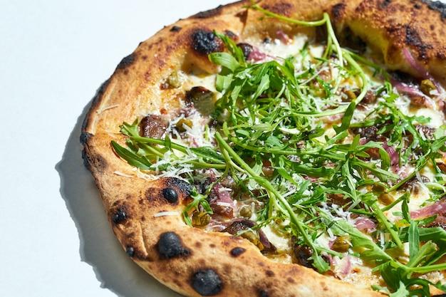 Délicieuse pizza italienne au feu de bois avec sauce crémeuse, pleurotes, câpres, roquette et truffe sur une surface grise. lumière forte.