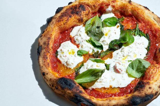 Délicieuse pizza italienne au feu de bois avec sauce tomate, stracatella et basilic sur une surface grise. lumière forte.