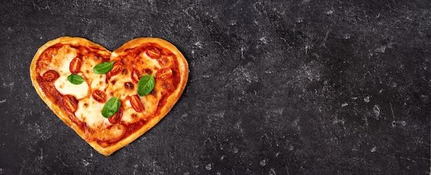 Délicieuse pizza italienne en forme de coeur sur fond noir