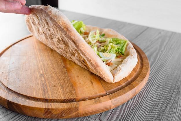 Délicieuse pizza italienne fraîche avec jambon, salami, tomates, salade, œuf de caille et parmesan sur une planche de bois sur une table en bois. pâte à pizza parfaite.