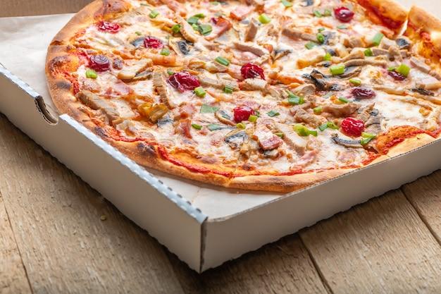 Délicieuse pizza italienne avec fromage mozzarella, tomates, bacon, champignons et oignon vert