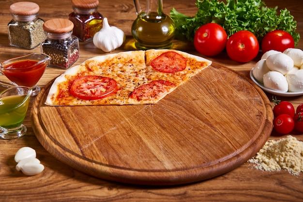 Délicieuse pizza italienne tranchée servie sur une table en bois. pizza margarita à la sauce tomate, mozzarella fraîche, parmesan sur le bois rouillé