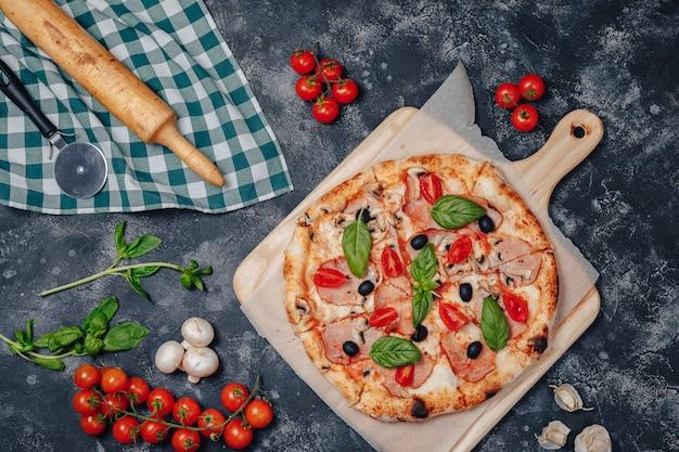 Délicieuse pizza napolitaine à bord avec des tomates cerises