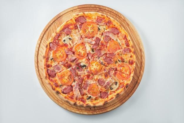 Délicieuse pizza avec sauce rouge, saucisses fumées, tomates et champignons sur un plateau en bois. fond blanc. cuisine italienne