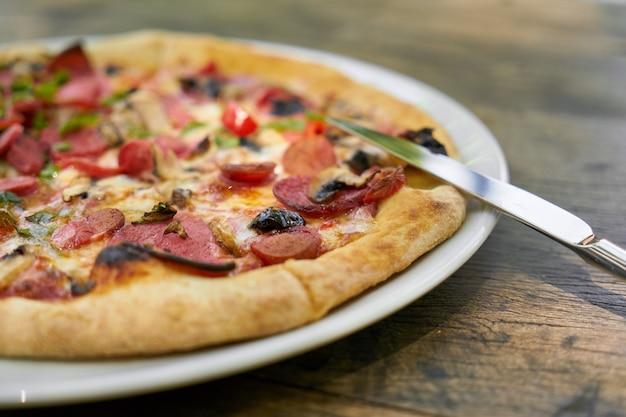 Délicieuse pizza servie dans une assiette en porcelaine