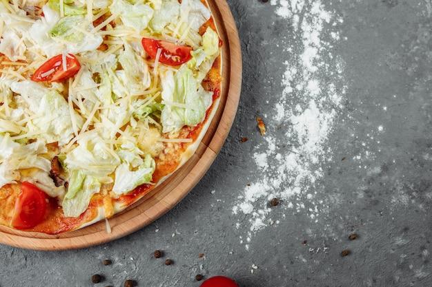 Délicieuse pizza style césar avec sauce blanche, poulet, parmesan, oeuf, tomates cerises et laitue fraîche à fond en bois