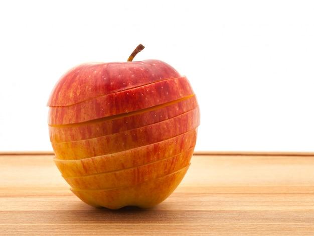 Une délicieuse pomme juteuse pour la cuisson coupée en travers sur une table en bois.