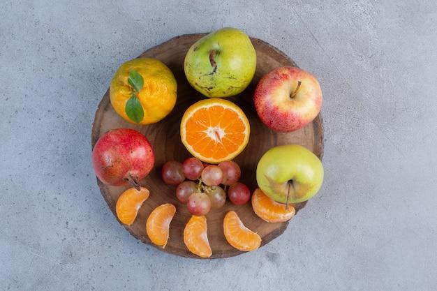 Une délicieuse portion de fruits sur une planche de bois sur fond de marbre.