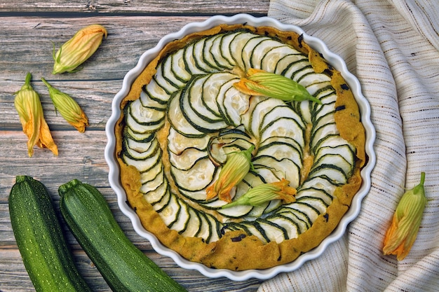 Délicieuse quiche aux courgettes et fromage fait maison sur un plat blanc entouré de fleurs