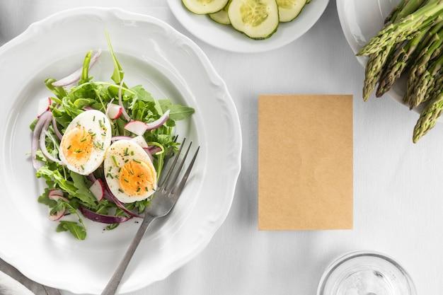 Délicieuse salade sur une assiette blanche avec carte vide
