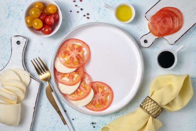 Délicieuse salade caprese avec tomates mûres et fromage mozzarella, feuilles de basilic frais, huile d'olive et sauce balsamique. nourriture italienne. vue de dessus plat lapointe sur fond bleu