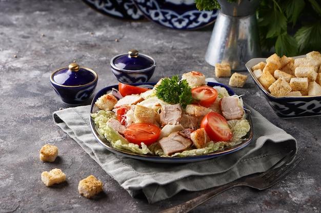 Délicieuse salade césar avec poulet, chou, œufs et pain grillé servi en assiette