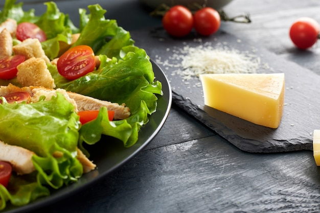 Délicieuse salade césar avec tomates cerises et croûtons et morceau et parmesan râpé