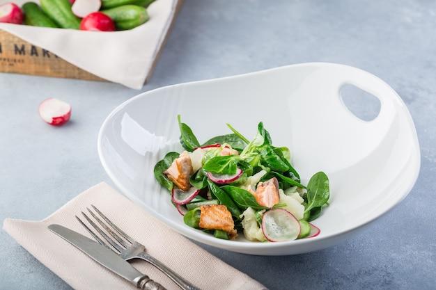 Délicieuse salade fraîche avec du poisson rouge et des légumes. salade chaude au saumon dans une assiette blanche avec des couverts sur une table de restaurant.