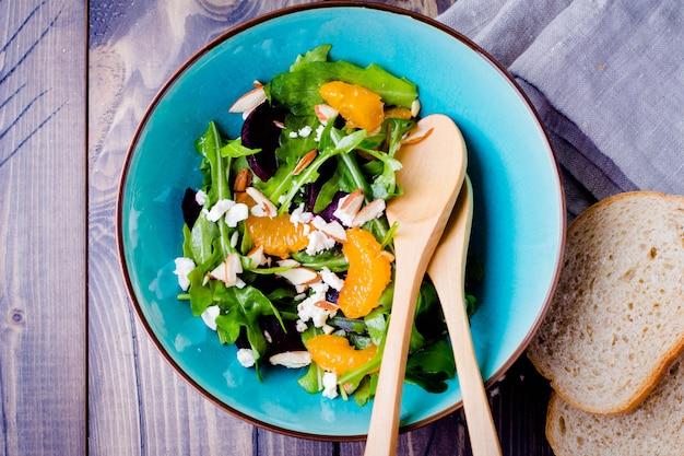 Délicieuse salade de fruits et légumes avec mandarine, betteraves, fromage feta, roquette et noix de noix dans l'assiette