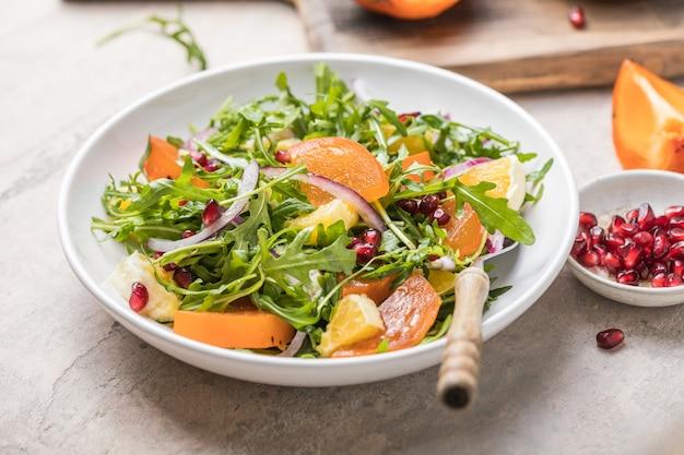 Délicieuse salade de kaki à la roquette et à l'orange servie sur une table gris clair, à plat. espace pour le texte
