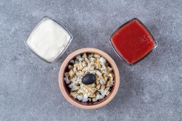 Délicieuse salade avec mayonnaise et ketchup sur fond gris. photo de haute qualité
