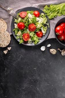 Délicieuse salade sur une plaque sombre avec copie espace