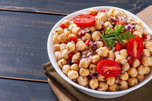 Délicieuse salade de pois chiches aux tomates, oignons, poivrons et persil, copy space