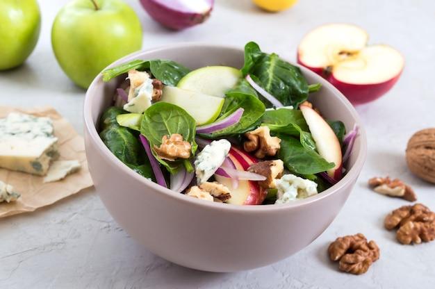 Délicieuse salade de remise en forme diététique aux épinards, pommes, oignons rouges, fromage bleu, noix