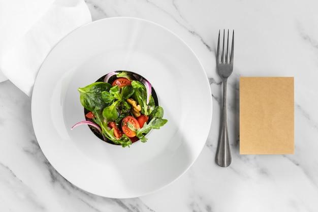 Délicieuse salade saine sur un assortiment de plaques blanches