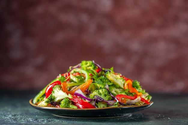 Délicieuse salade végétalienne avec des ingrédients frais dans une assiette sur fond flou bleu et marron