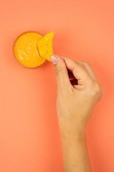 Délicieuse sauce au fromage avec nachos. une main féminine abaisse le triangle des nachos avec de la sauce.