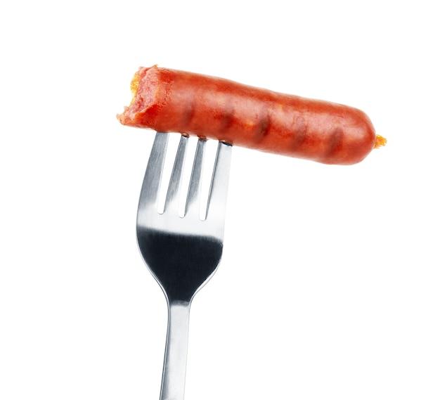 Délicieuse saucisse sur une fourchette, isolée sur fond blanc