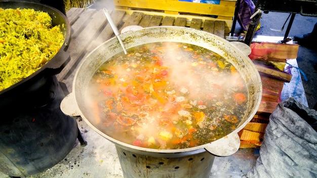 Délicieuse soupe bouillante dans une grande poêle en métal en feu