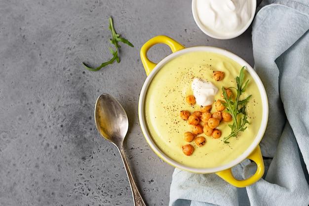 Délicieuse soupe de chou-fleur au curry et à la crème dans un bol garnir de pois chiches grillés et de roquette