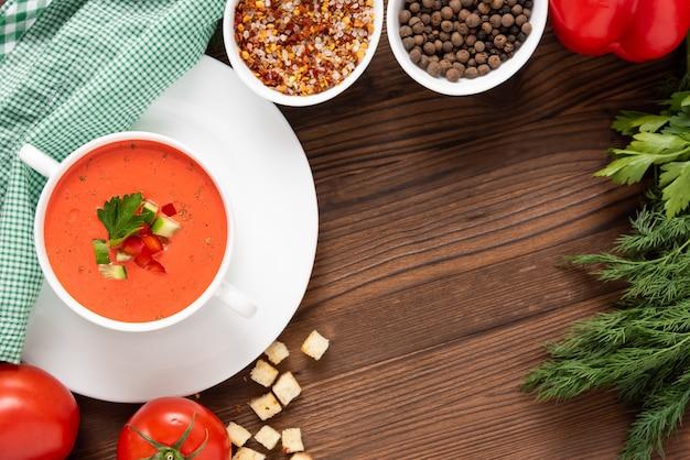 Délicieuse soupe à la crème de tomates sur un fond en bois avec des herbes et des croûtons. dans un bol à soupe.