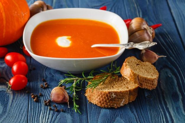 Délicieuse soupe de potiron à la crème épaisse sur une table en bois rustique foncé